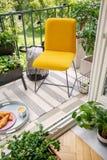Cadeira amarela vibrante e plantas home em um balcão calmo com luzes da corda, o café da manhã doce e um listrado fotos de stock royalty free