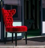Cadeira antiquado vermelha na frente da entrada da loja Imagem de Stock Royalty Free