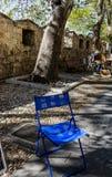 Cadeira azul do ` s do pintor em uma aleia obscuro Entrada à cidade velha em Rhodes Town, Grécia Imagem de Stock Royalty Free
