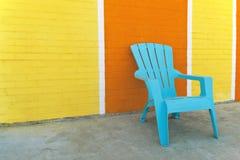 Cadeira azul na frente de uma parede de tijolo colorida Imagens de Stock Royalty Free