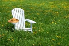 Cadeira branca com chapéu de palha Imagens de Stock