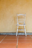 Cadeira branca do vintage perto da parede velha amarela fotografia de stock