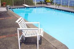 Cadeira branca pelo lado da piscina privada Imagens de Stock Royalty Free