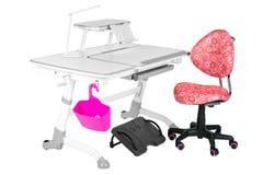 Cadeira cor-de-rosa, mesa cinzenta da escola, cesta cor-de-rosa, lâmpada de mesa e apoio preto sob os pés Imagens de Stock Royalty Free