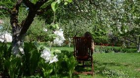 A cadeira da mulher relaxa o jardim vídeos de arquivo