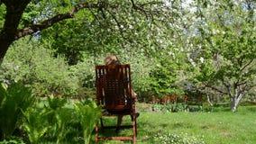 A cadeira da mulher relaxa o jardim filme