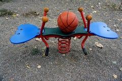 Cadeira de balanço das crianças borboleta-dada forma e um basquetebol em um parque para crianças fotografia de stock royalty free
