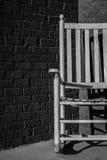 Cadeira de balanço de madeira contra uma parede de tijolo Foto de Stock