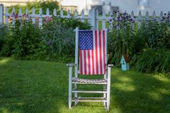 Cadeira de balanço de madeira velha rústica que senta-se na jarda com a bandeira dos EUA em b Imagens de Stock