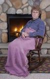 Cadeira de balanço triste da face da mulher sênior madura, incêndio Fotos de Stock Royalty Free