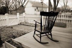 Cadeira de balanço velha no patamar de madeira com a cerca de piquete branca. Foto de Stock