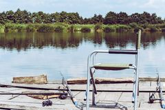 Cadeira de dobradura, haste para pescar no cais de madeira no beira-rio Imagem tonificada retro do equipamento de pesca fotografia de stock royalty free