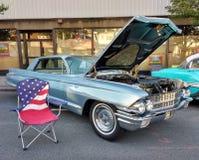 Cadeira de gramado da bandeira americana perto de um carro clássico em um Car Show Foto de Stock Royalty Free