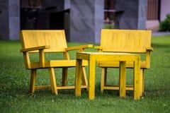 A cadeira de madeira amarela no jardim fotografia de stock