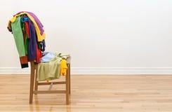 Cadeira de madeira com roupa desarrumado nela Imagem de Stock Royalty Free