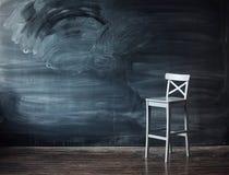 Cadeira de madeira de encontro a uma mesa da escola para a letra imagens de stock