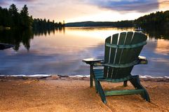 Cadeira de madeira no por do sol na praia Fotos de Stock Royalty Free