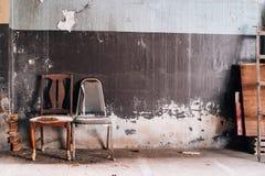 Cadeira de madeira velha na parede Fotos de Stock Royalty Free