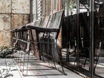 Cadeira de madeira velha situada na frente da construção velha fotografia de stock royalty free