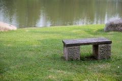 Cadeira de pedra perto do lado do rio fotos de stock royalty free