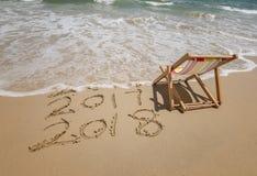 Cadeira de plataforma com a inscrição 2018 e 2017 escrita na areia Fotografia de Stock