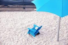 Cadeira de plataforma pl?stica azul e parasol pl?stico ciano nas areias brancas de uma praia foto de stock