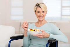 Cadeira de rodas da mulher que come a salada imagem de stock royalty free