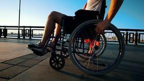 Cadeira de rodas de Guy With Diseased Legs On que anda com a amiga na margem na noite do verão filme