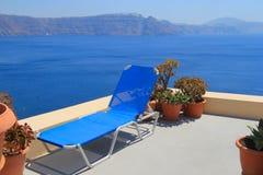 Cadeira de sala de estar azul contra o mar, Santorini imagens de stock royalty free