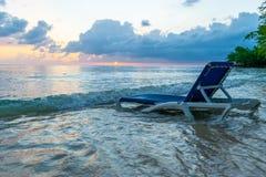 Cadeira de sala de estar da praia na água no litoral branco bonito da areia como a luz dos céus começa a incandescer no por do so fotografia de stock royalty free