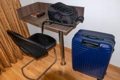 A cadeira de tabela com leva o saco e a mala de viagem dentro da sala fotos de stock royalty free