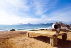Cadeira do Driftwood no mar Fotos de Stock