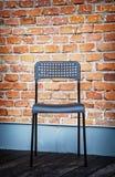 Cadeira do metal na frente da parede de tijolo Imagens de Stock