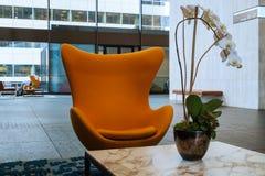 Cadeira do ovo e planta alaranjadas da orquídea no prédio de escritórios Imagens de Stock Royalty Free