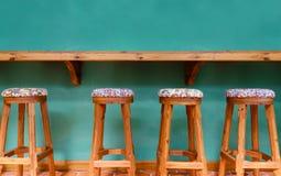 Cadeira do tamborete de madeira do vintage no fundo verde Imagens de Stock Royalty Free