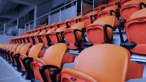 Cadeira dos assentos da arena do estádio Fileiras do assento espectador alaranjado em um estádio dos esportes vídeos de arquivo