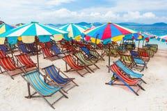 Cadeira e guarda-chuvas de praia na praia fotografia de stock royalty free