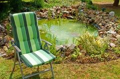 Cadeira e lagoa de jardim Fotografia de Stock