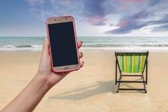A cadeira e a sombra de praia na areia branca encalham com luz do por do sol Foto de Stock
