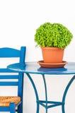 Cadeira e tabela azuis com flowerpot da manjericão fotos de stock