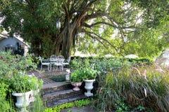 Cadeira e tabela brancas do ferro forjado no jardim na manhã Fotografia de Stock