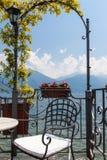 Cadeira em um terraço que negligencia o lago e montanhas calmos no af fotografia de stock