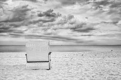 Cadeira encapuçado da cesta de vime na praia vazia Fotos de Stock