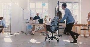 A cadeira fêmea bem sucedida da equitação do líder da equipe do movimento lento ao longo do escritório, executivos do divert filme