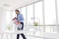 Cadeira levando do homem de negócios maduro envolvida no plástico no escritório novo imagens de stock