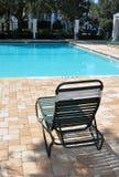 Cadeira na frente de uma piscina Fotografia de Stock Royalty Free