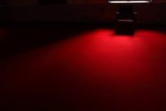 A cadeira na obscuridade no tapete vermelho imagens de stock