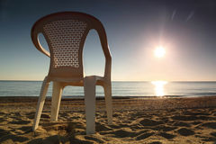 A cadeira plástica está lateralmente na praia perto do mar Imagens de Stock
