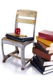 Cadeira, portátil e pilha da velha escola de livros imagens de stock royalty free