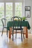 Cadeira preta ao lado de uma tabela com pano verde em um interior da sala de jantar Janela do balcão no fundo fotos de stock
